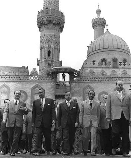 Several men walking forward, side-by-side. There are five men in the forefront, all wearing suits and ties. In the background is an ornate building with two minarets and a dome.