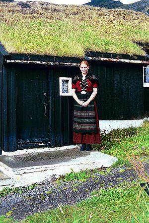 Norðragøta - The famous Faroese singer Eivør Pálsdóttir posing in national costume in front of the museum Blásastova in Gøta.