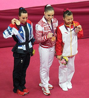 Aliya Mustafina - Mustafina (center) holding her gold medal from the 2012 Olympic uneven bars final along with the silver and bronze medalists, He Kexin (right) and Beth Tweddle.