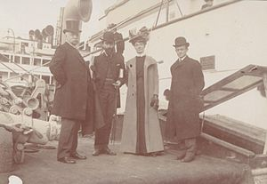 William Henry Goodyear - Four people including Goodyear in front of a ship. Possibly taken before or after 1901 survey expedition.