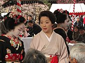 A geisha wearing a plain pink kimono with no white face makeup stood to the right of a maiko in full makeup wearing a heavily-decorated black kimono