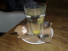 A glass with a spoon and cubed sugar on a wooden table