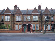 A row of two-storey red brick houses with sharply angled roofs and large windows