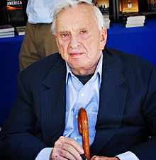 Gore Vidal in 2008 seated and holding a cane and pen.