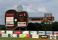 A view of the giant black guitar-shaped scoreboard beyond the left-center field wall. Advertisements for local businesses adorn the guitar and the green outfield wall below.