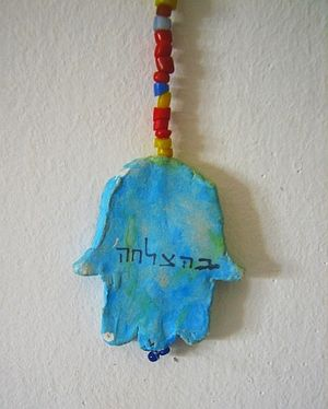 "Hamsa - Clay hamsa with an inscription in Hebrew (translates to ""good luck"")"