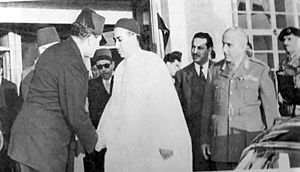 Hussein Maziq - Crown Prince Hasan (in white) shaking hands with Governor Hussein Maziq. Wanis al-Qaddafi and General Buguaitin are standing behind the prince.
