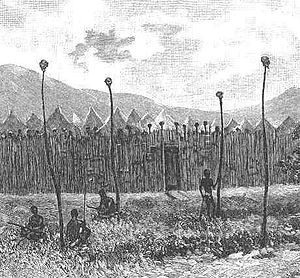 Stairs Expedition to Katanga - The front of Msiri's boma (compound) at Bunkeya. The objects on top of the four poles, below which some of Msiri's warriors are gathered, are heads of his enemies. More skulls are on the palisades forming the stockade.