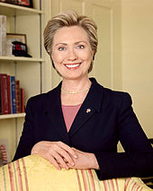 Clinton's official photo as U.S. senator. She is wearing a black suit with a pink shit underneath, and is smiling at the camera while standing behind a chair with yellow upholstery, with her hands folded together upon the chair's back.
