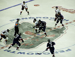 Players on two teams, one in white and the other in dark blue, face off against each other while a referee prepares to begin play
