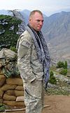 A white man with close-cropped blond hair standing with his hands in his pockets, wearing a camouflage uniform and a long blue and white scarf hanging untied around his neck. Behind him are a wall of sandbags, a tree and, in the distance, mountains.