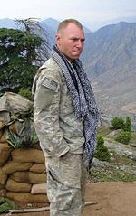 A man in his camoflouge military uniform wearing a scarf around his neck. He is looking at the camera and has his hands in his pockets. Several mountains are visible in the background.
