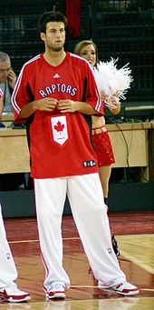 "A man, wearing white pants and a red t-shirt with the word ""RAPTORS"" on the front, is standing on a basketball court."