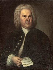 portrait of Bach towards the end of his life, posing in a dark outfit with a wig, holding a single sheet of music in his right hand, facing the viewer with a serious expression