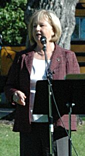 A photograph of a blonde woman wearing a white shirt, a purple jacket, and black dress pants standing in front of a black microphone