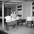 Kinderverzorgster met een baby bij een wieg op een veranda, Bestanddeelnr 252-9112.jpg