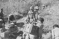 Unarmed men with boxes of supplies strapped to their backs at the bottom of a hill. In the background other men have begun the climb to the top.
