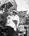 Kvinna sitter på stenmur med spädbarn i famnen. Fiskebäckskil, Bohuslän - Nordiska Museet - NMA.0054138.jpg