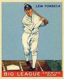 A baseball card image of a man in a white old-style baseball uniform and a navy-blue baseball cap following through on a swing with the bat toward his left shoulder