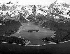 Lituya Bay - Oblique aerial photograph of Lituya Bay in the Summer of 1958.  Damage from the 1958 megatsunami appears as the lighter-colored areas on the shores where trees have been stripped away.