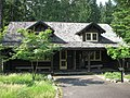 Photograph of the Hiker's Center, one of the Longmire Buildings at Mount Rainier National Park on a late spring day, a low, rustic, log building with a patch of long grass in front and deep green forest behind.