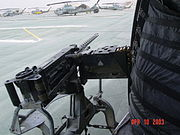 view from inside a helicopter out a door to a corwded tarmac