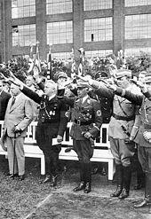 Kuva: Kuningas keskellä ihmisiä, jotka ojentavat kätensä Hitlerin tervehdyksessä