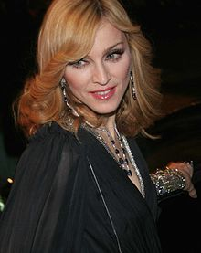 Madonna in a black dress and golden curls, looks towards her right. She wears bangles in her left hand