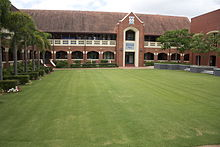 A green quadrangle surrounded by red brick buildings.