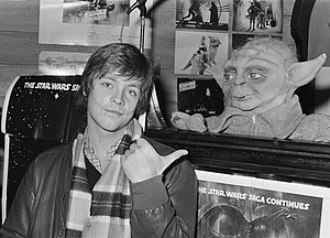 A black and white photograph of a young man pointing to a Yoda puppet while surrounded by Star Wars memorabilia.