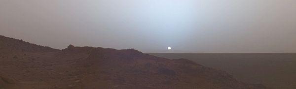 Zdjęcie panoramiczne. Na pierwszym planie skaliste wzniesienie, za nim równina. Na horyzoncie okrągła biała tarcza Słońca z niebieską poświatą.