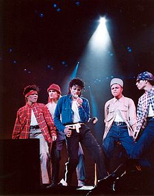 Under a spotlight, a man sings into a microphone. He is surrounded by four male dancers dressed up to look aggressive. The man himself wears black pants held up by a white sash, as well as a white T-shirt, and an opened blue shirt, which is tucked into his pants.