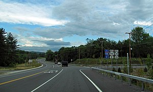 "A two-lane paved road curves gently ahead of the viewer in a mostly wooded area under a mostly cloudy sky. There is a left-turn lane immediately ahead and another road leaving at a right angle to the right, going slightly uphill, with steel guardrails on the right. Black and white signs at the right identify the road ahead as ""30A"", the road to the right as ""30"", and state that the road ahead will lead the driver to an ""88"", signed in red, white and blue"