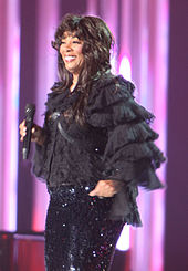 With long brown hair, a woman smiles and holds a microphone, wearing a black outfit.