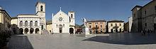 Piazza San Benedetto: al centro della foto la basilica di San Benedetto con a destra il portico delle misure. A sinistra il palazzo comunale. Al centro della piazza la statua del santo.