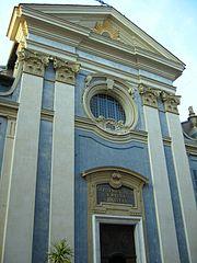 Vue d'une façade néoclassique bleue avec colonnades blanches et fronton décoré depuis la rue.