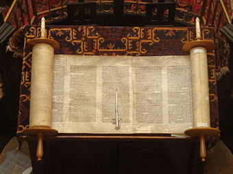 The Torah is the primary sacred text of Judaism. Open Torah and pointer.jpg