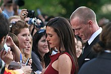 A brown hair woman signs autographs for fans. She wears a red dress. Behind her there is a blond man dressed with a suit. The woman and the man are facing a crowd of fans.