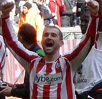 A man wearing a red and white football shirt after a game; with his arms raised triumphantly.