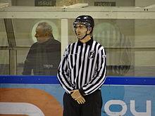 Photographie de Pierre Dehaen en tenue d'arbitre lors d'un match de hockey sur glace