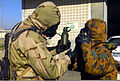 Preparing to take a drink with some help, an Australian adjusts his with Avon FM12 Mask so his Marine partner can pull out the canteen adapter 020121-M-BH370-011.jpg
