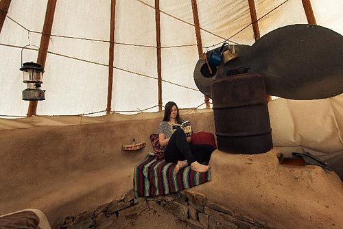 This is a rocket mass heater inside of a tipi at Paul Wheaton's permaculture homestead in Montana