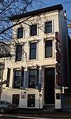 foto van Deftig herenhuis met hoge, in pleister gebosseerde lijstgevel. Hardstenen onderpui; vensters en bel-etage en verdieping met hoofdgestellen op consoles