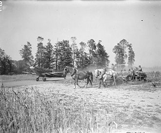 Advanced Landing Ground - A Spitfire Mark IX of No. 443 Squadron RCAF taxies to dispersal at B-2 Bazenville, alongside a field where French farmers are gathering in the wheat