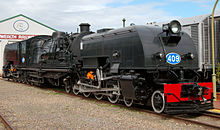 Front oblique view of a black steamtrain with a blue-and-white number 409 on the front and a large shed visible behind.