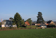 Several houses and school behind fields and hedgerows.