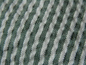 Seersucker - Close-up of green/white striped seersucker fabric showing the weave details.