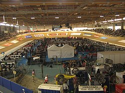 Inside the arena with bikes, cyclists and mechanics on the inside of the track