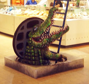 Sewer alligator - A model of an alligator emerging from a sewer manhole in a mall.