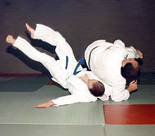 Judoka demonstrate a dynamic soto-makikomi